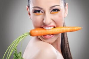 Funny image of woman showing carrot,  Healthy lifestyle people.